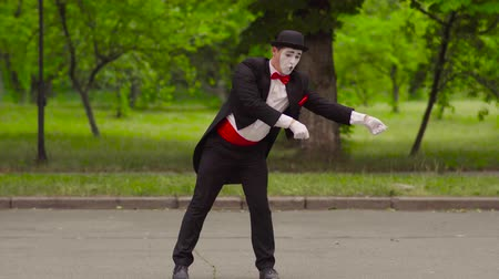greasepaint : Mime catches his colleague with invisible lasso in the park Stock Footage