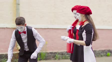 comics : Three funny mimes play joking scenes on city street