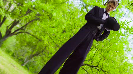 akt : Handsome man in costume walks on stilts at the park near tree