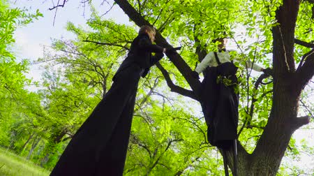 pulling off : Mime and street artists fooling on stilts play in the park