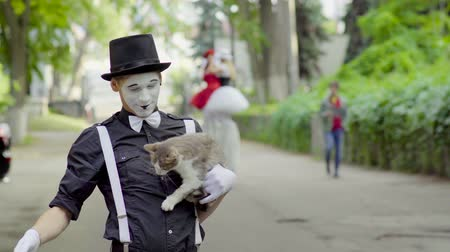 gesticulando : Funny mime joking with cat on the street