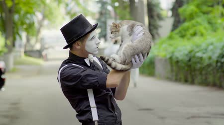 greasepaint : Comic mime joking with cat on the street Stock Footage