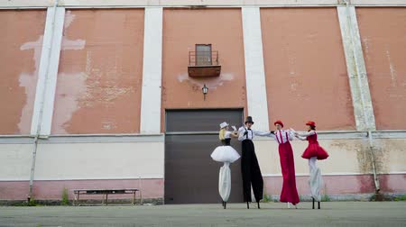 színésznő : Two comic couples on stilts are dancing near the building Stock mozgókép