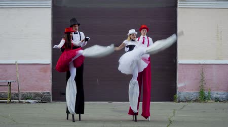 korzet : Two funny couples on stilts are dancing near the building