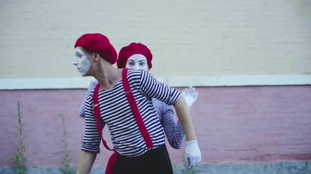 greasepaint : Two mimes in striped clothes make funny moves near building Stock Footage
