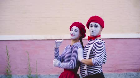 greasepaint : Two mimes dance near wall of building Stock Footage