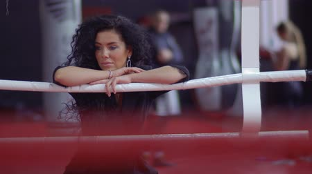feminity : Beautiful curly brunette stand near the ring