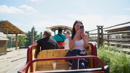 avestruz : Group of people ride open car at the contact zoo
