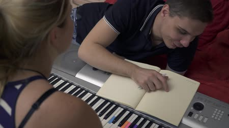 поглаживание : Handsome guy and beautiful blonde girl near the synthesizer together