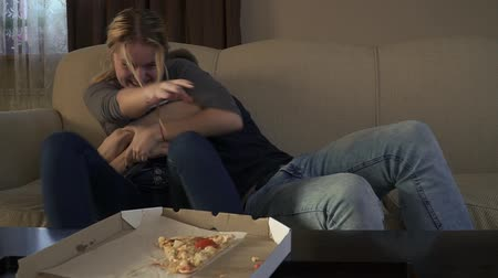 picture box : Attractive young couple sitts on the couch near to pizza