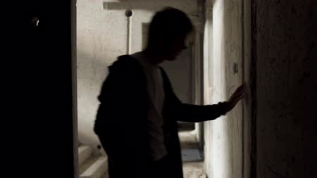 narcomaniac : Yound bad looking man leans against the walls in an abandoned building