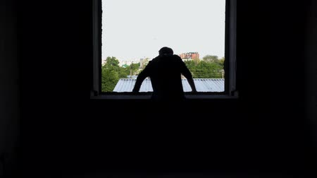 homály : Yound bad looking man looks out the window of an abandoned house Stock mozgókép
