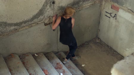 narcomaniac : Drug addict descends the stairs in an abandoned building Stock Footage