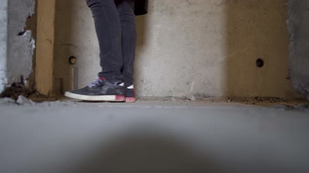 narcomaniac : Legs of a man in sneakers on the background of an abandoned building