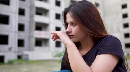 miserável : Nervous brunette girl is sitting near high building