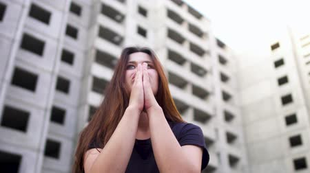 narcomaniac : Crazy looking girl is sitting near high building and praying to the sky