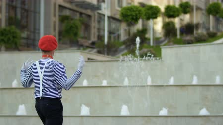performer : Funny mime conductor gesticulating hands at fountain background