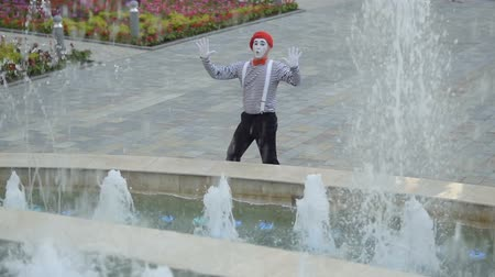 gesticulando : Funny mime in red beret touching invisible wall near fountains