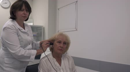 понимание : Medical professional tests the ear of an adult woman