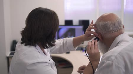 listens : Medical professional tests the ear of an adult man
