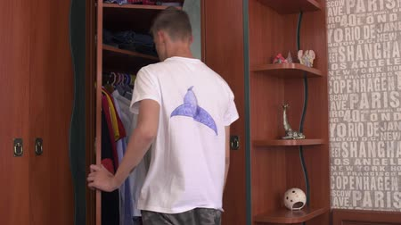 nagy : The boy chooses clothes in the closet