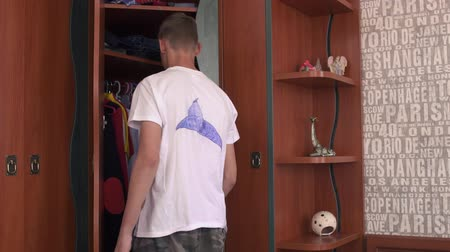 raflar : The boy chooses clothes in the closet