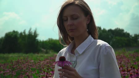 temperada : Beautiful brunette on a flower field sniffing a flower Stock Footage