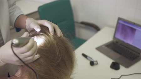 aseptic : Dermatologist examines the skin on the head of the girl
