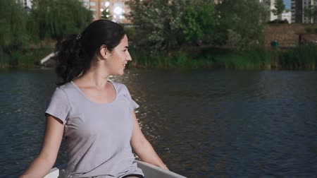 гребля : Beautiful young girl is sitting in a boat