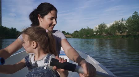 kürek çekme : Mother and daughter rowing in the boat Stok Video