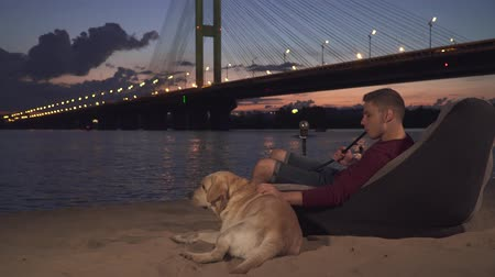 fuma : Young guy sits with a dog on the beach and smokes a hookah Vídeos