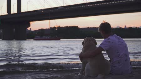 гладильный : Young guy is sitting with a dog on the river bank