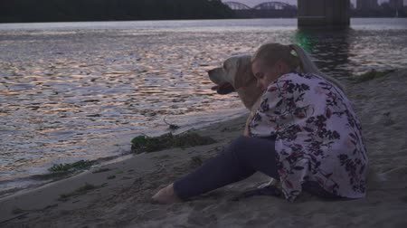 гладильный : Beautiful girl walks with a dog on the river bank