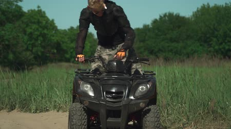 appear : Young teenage man is sitting on ATV