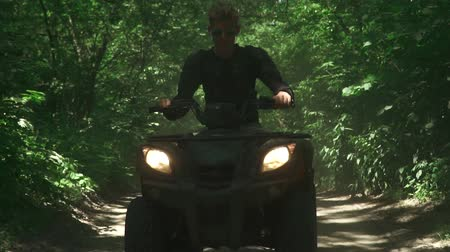 adrenalina : Young man drives ATV in the forest