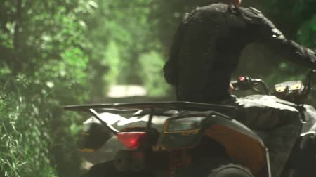 quadbike : Young man drives ATV in the forest