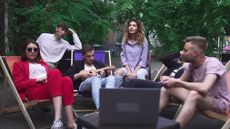 нетбук : Company of young people have a rest in a summer cafe