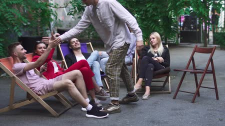 нетбук : Company of young people is resting on a summer area in a cafe Стоковые видеозаписи