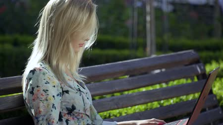 denim : Beautiful girl is sitting on a bench in the park Stock Footage