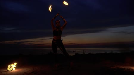 племенной : Beautiful woman dances with fire near the river at the night