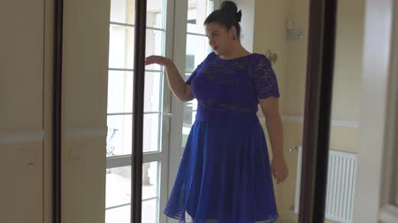 tamanho : Fat girl in a blue dress in front of a mirror