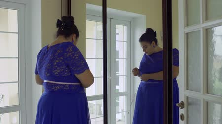 paunchy : Fat girl in a blue dress in front of a mirror