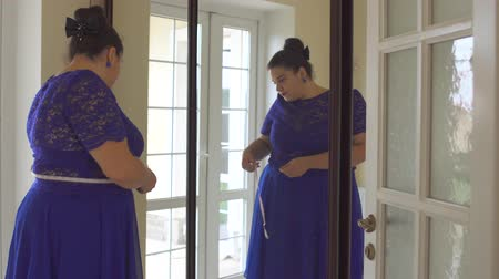etli : Fat girl in a blue dress in front of a mirror