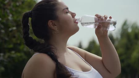 etli : Fat girl drinks water from a bottle Stok Video