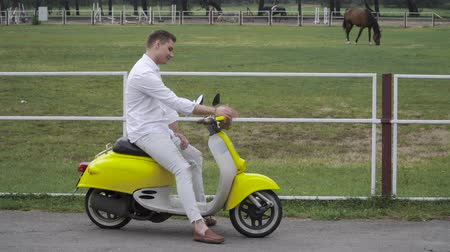 jazda konna : Young guy sits on a moped and looks at the horses