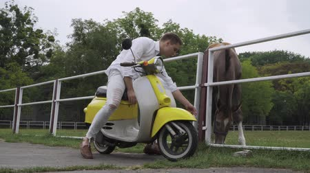 tahy : Young guy sits on a scooter and strokes a horse