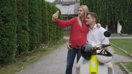 robogó : Couple makes a selfie near the motorbike