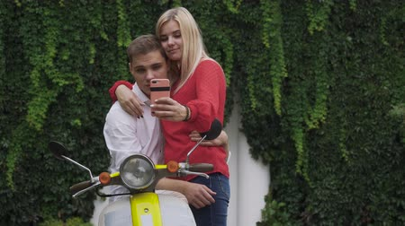 skútr : Beautiful couple makes a selfie on the motorbike