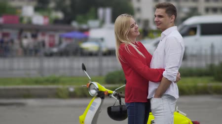mladistvý : Teenagers hugging near a scooter