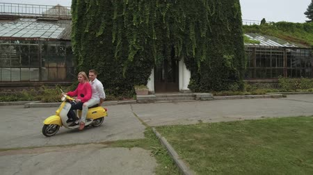 skútr : Beautiful couple riding a scooter in the park. Shot on drone